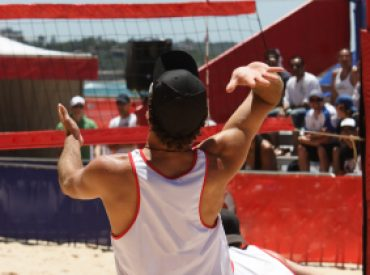 A beach volleyball player serving